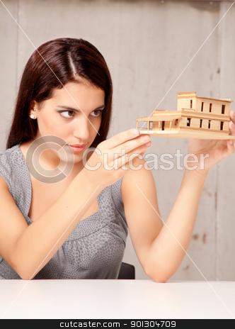 Designer Examining Model House stock photo, An architect designer examining a rough model house of wood by Tyler Olson