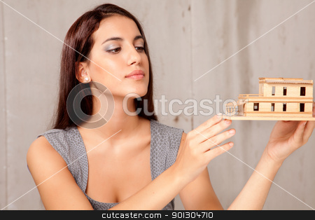 Female Architect with House Model stock photo, A young female architect or designer looking at a rough house model by Tyler Olson