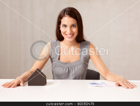 Real Estate Agent stock photo, A conceptual housing market shot, a woman with model house and Euro money by Tyler Olson