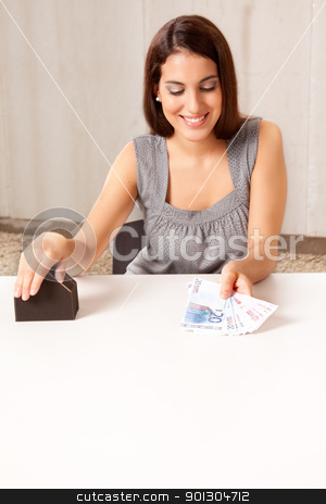 Real Estate Purchase stock photo, A woman holding out money (euro) in exchange for a house by Tyler Olson