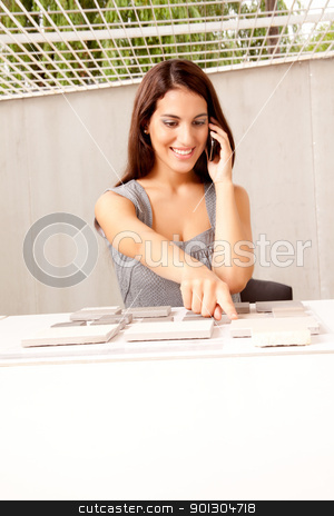 Architect Choosing Stone Tile stock photo, An architect on the phone choosing a stone tile swatch by Tyler Olson