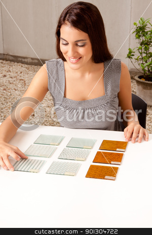 Choosing Tile Sample stock photo, A female architect / designer choosing a glass tile from a group of samples by Tyler Olson