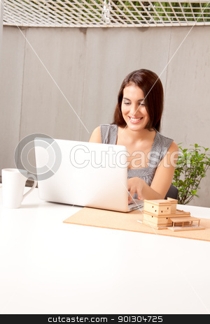 Architect using Computer stock photo, An architect using a laptop computer with a model house on the desk by Tyler Olson