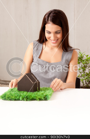 Green Architecture stock photo, A happy professional woman looking at a model house with grass by Tyler Olson