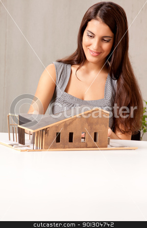 Female Architect with House Model stock photo, A female architect building a rough house study model by Tyler Olson