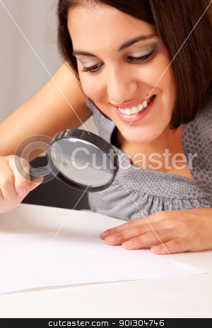 Woman with Magnifying Glass stock photo, A prety brunette woman looking at a paper with a magnifying glass by Tyler Olson