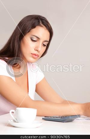 Woman Calculating Finances stock photo, A woman sitting at a desk calculating finances by Tyler Olson