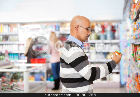 Mature man shopping in the supermarket stock photo, Mature man shopping in the supermarket with people in the background by Tyler Olson