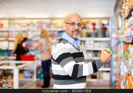 Man in Grocery Store stock photo, Portrait of a mature man shopping in the supermarket with people in the background by Tyler Olson