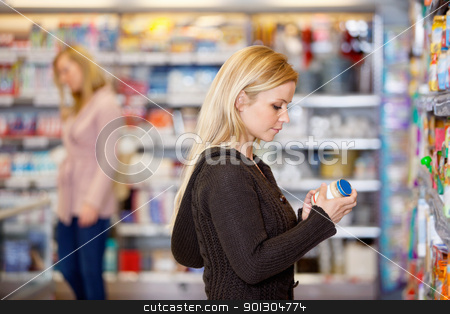 Young Woman Product Compare stock photo, Young woman comparing products in the supermarket with people in the background by Tyler Olson