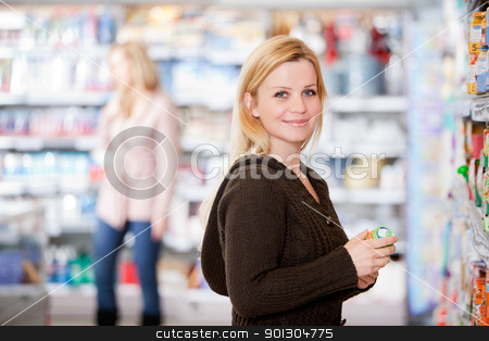 Woman in Grocery Store stock photo, A young woman buying groceries in a grocery store by Tyler Olson