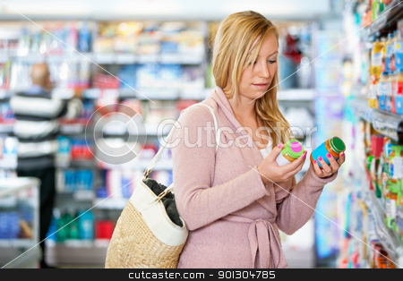 Young woman holding jar in the supermarket stock photo, Young woman holding jar in the supermarket with people in the background by Tyler Olson