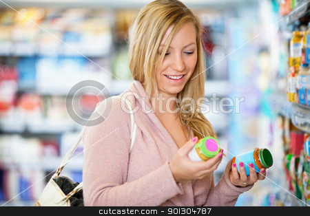 Closeup of a young woman smiling while holding jar stock photo, Closeup of a young woman smiling while holding jar in the supermarket by Tyler Olson