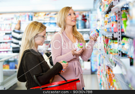 Product Comparison stock photo, Young women shopping together in the supermarket with people in the background by Tyler Olson