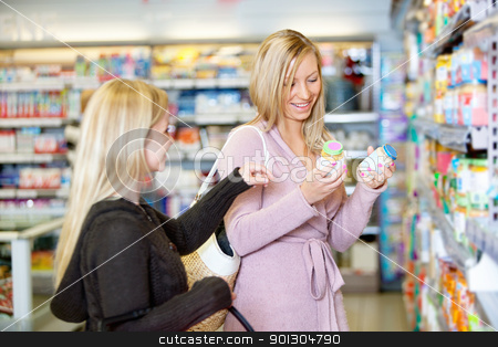 Young women smiling while shopping together stock photo, Young women smiling while shopping together in the supermarket by Tyler Olson