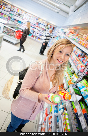 Product Comparison Grocery Store stock photo, Happy young woman holding jar in the supermarket with people in the background by Tyler Olson