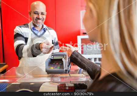 Grocery Store Cashier stock photo, Woman passing over credit card to shop assistant after shopping by Tyler Olson