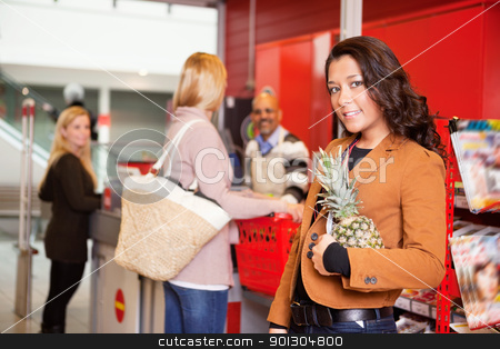Portrait of a customer carrying pineapple stock photo, Portrait of a customer carrying pineapple in supermarket with people in the background by Tyler Olson