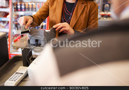 Shop assistant swiping credit card stock photo, Shop assistant swiping credit card in supermarket with customer in the foreground by Tyler Olson