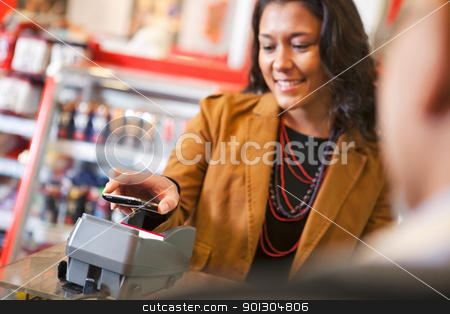 Pay with Cell Phone stock photo, Young woman paying for purchase with cell phone by Tyler Olson