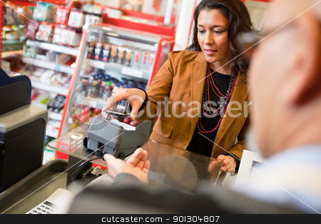 Mobile Payment stock photo, A young woman paying for grocery purchase with a mobile phone by Tyler Olson