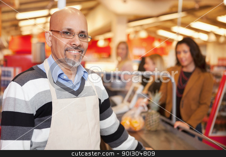 Supermarket Cashier Portrait stock photo, Portrait of a happy cashier with customer in the background by Tyler Olson