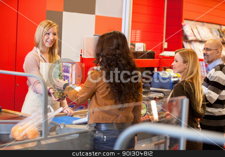Supermarket Cashier Line stock photo, View of happy shop assistant with customer in supermarket holding pineapple by Tyler Olson