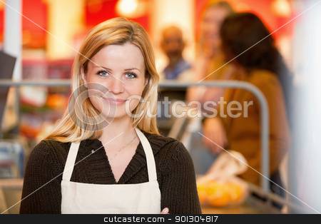 Portrait of a young shop assistant stock photo, Closeup of a young shop assistant with customer in the background by Tyler Olson