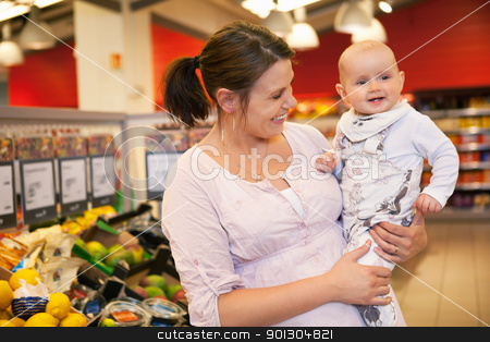 Happy mother carrying child stock photo, Happy mother carrying child in supermarket by Tyler Olson