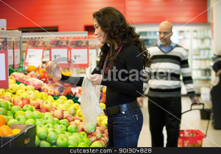Woman Buying Fruit stock photo, Young woman buying fruits in the supermarket with man in the background by Tyler Olson