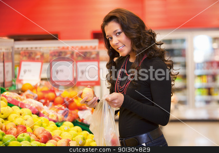 Portrait of a young woman buying fruits stock photo, Portrait of a young woman buying fruits in the supermarket by Tyler Olson