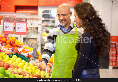 Woman Buying Groceries stock photo, A woman buying groceries receiving help from a store clerk by Tyler Olson