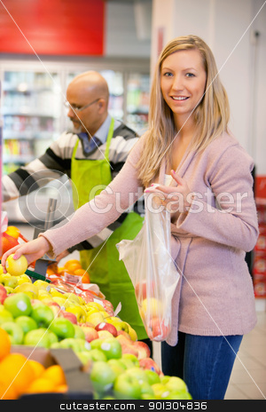 Portrait of a young woman buying fruits stock photo, Portrait of a young woman buying fruits with shop assistant in the background by Tyler Olson