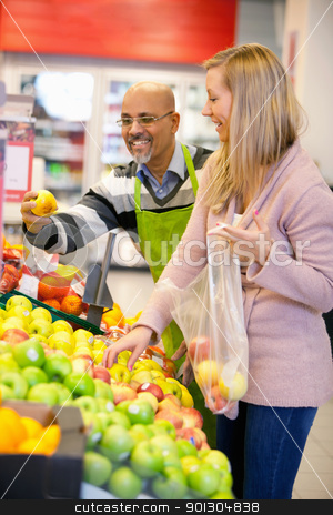 Happy young woman buying fruits stock photo, Happy young woman buying fruits with shop assistant in the background by Tyler Olson