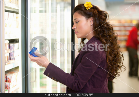 Woman in Supermarket stock photo, Young woman holding container in front of refrigerator in the supermarket by Tyler Olson