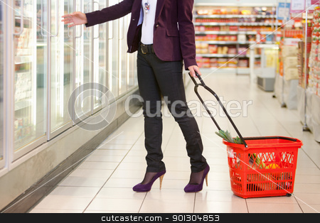 Grocery Store Cooler stock photo, Low section of woman in front of refrigerator carrying basket in the supermarket by Tyler Olson