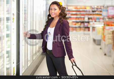 Cold Food Supermarket stock photo, Portrait of a young woman opening refrigerator in the supermarket by Tyler Olson