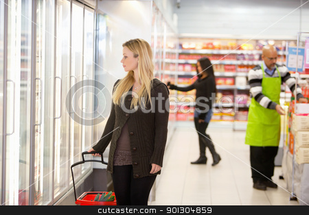 Supermarket Grocery Store stock photo, Woman in shopping mall looking through cooler window with people in the background by Tyler Olson