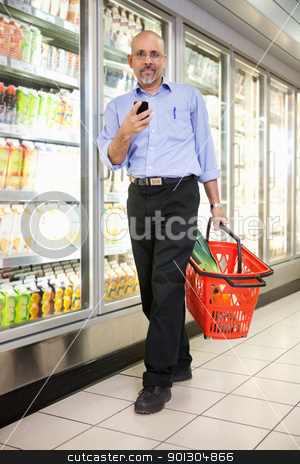 Man in Supermarket stock photo, Full length of mature man in shopping store carrying basket and using mobile phone while walking by Tyler Olson
