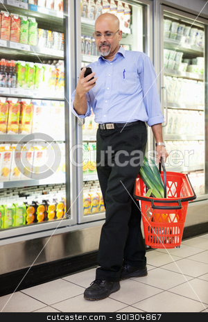 Man with Grocery Basket and Mobile Phone stock photo, Man with shopping basket looking at cell phone while walking in shopping store by Tyler Olson