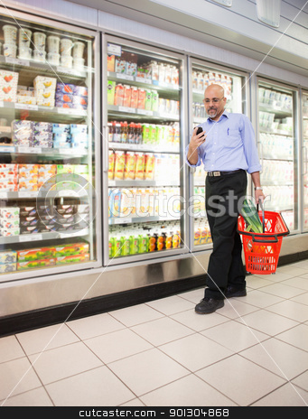 Supermarket Cell Phone stock photo, Mature man looking at mobile phone while walking in front of refrigerators in shopping centre by Tyler Olson
