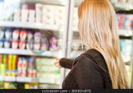 Faceless Woman in Supermarket stock photo, Close-up of woman reaching for products arranged in refrigerator by Tyler Olson