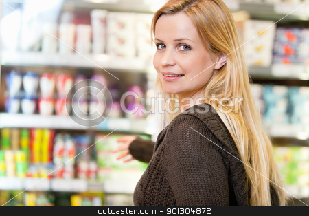 Portrait of Woman in Supermarket stock photo, Close-up of smiling woman reaching for products arranged in refrigerator and looking at camera by Tyler Olson