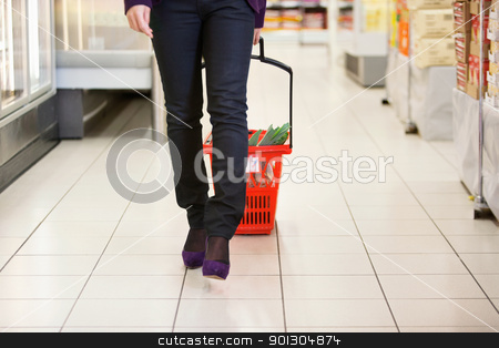 Woman Walking with Shopping Basket stock photo, Low section of female walking with shopping basket in shopping store by Tyler Olson