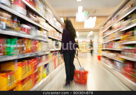Woman looking at products in shopping store stock photo, Blurred view of woman looking at products with people in the background in shopping centre by Tyler Olson