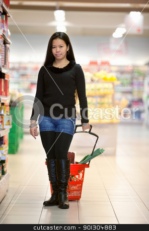 Portrait of woman holding basket in shopping centre stock photo, Full length of woman holding shopping basket in shopping centre and looking at camera by Tyler Olson