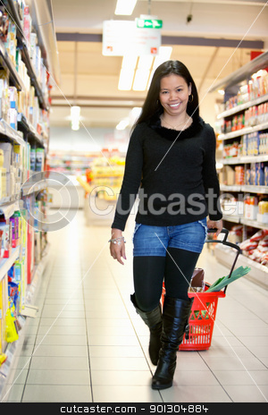 Asian Woman in Grocery Store stock photo, Full length of smiling woman in shopping centre pulling basket while walking and looking at camera by Tyler Olson