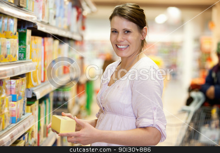 Young Female in Supermarket stock photo, Mid adult woman holding product and looking at camera in shopping centre by Tyler Olson