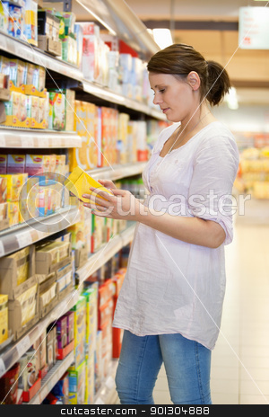 Woman looking at a product stock photo, Woman takes a product from shelves at a supermarket by Tyler Olson