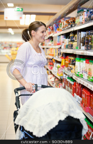 Mother with Carriage in Supermarket stock photo, Mid adult woman holding baby stroller and looking at products in shopping centre by Tyler Olson